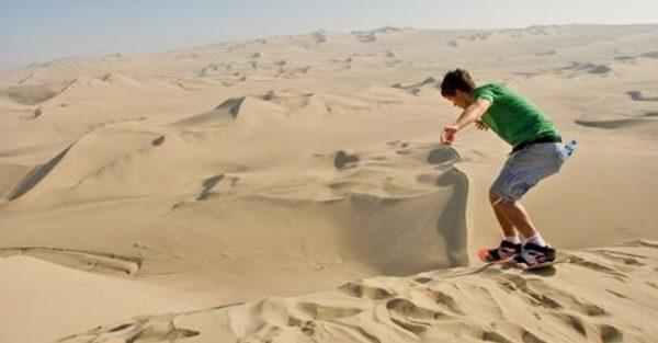Practicar sandboard en las dunas de Ica